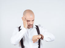 Ο φαλακρός επιχειρηματίας εξετάζει το ρολόι του Στοκ φωτογραφία με δικαίωμα ελεύθερης χρήσης