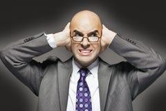 Ο φαλακρός επιχειρηματίας με παραδίδει τα αυτιά κοιτάζοντας λοξά Στοκ Εικόνα