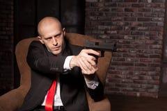 Ο φαλακρός δολοφόνος στο κοστούμι και τον κόκκινο δεσμό στοχεύει ένα πιστόλι Στοκ Εικόνες
