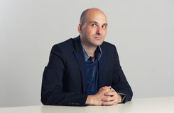 Ο φαλακρός τύπος κάθεται στο γραφείο Στοκ Εικόνα