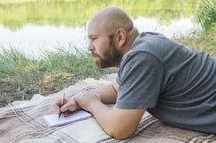 Ο φαλακρός τύπος στο πάρκο βρίσκεται σε μια χλόη Στοκ εικόνες με δικαίωμα ελεύθερης χρήσης