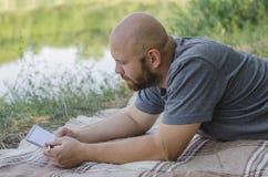 Ο φαλακρός τύπος στο πάρκο βρίσκεται σε μια χλόη Στοκ Εικόνες