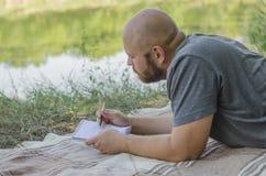 Ο φαλακρός τύπος στο πάρκο βρίσκεται σε μια χλόη Στοκ φωτογραφία με δικαίωμα ελεύθερης χρήσης
