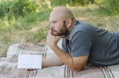 Ο φαλακρός τύπος στο πάρκο βρίσκεται σε μια χλόη Στοκ εικόνα με δικαίωμα ελεύθερης χρήσης