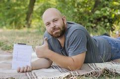 Ο φαλακρός τύπος στο πάρκο βρίσκεται σε μια χλόη Στοκ Φωτογραφίες