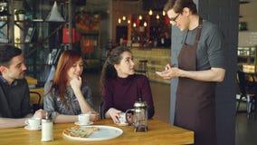 Ο φιλικός αρσενικός σερβιτόρος παίρνει τη διαταγή από την εύθυμη ομάδα φίλων που κάθονται στον πίνακα στον καφέ και την ομιλία να φιλμ μικρού μήκους