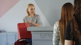 Ο φιλικός θηλυκός ταμίας παίρνει το ένδυμα από τη στάση πελατών στη γραμμή, την ερώτηση την για την πληρωμή, το δίπλωμα και τη συ φιλμ μικρού μήκους