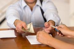 Ο φιλοξενούμενος πληρώνει το λογαριασμό και το ρεσεψιονίστ στο ξενοδοχείο που δίνει το κλειδί στο φιλοξενούμενο στοκ εικόνες