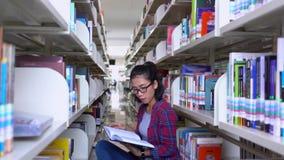 Ο φοιτητής πανεπιστημίου κάθεται στη βιβλιοθήκη διαβάζοντας απόθεμα βίντεο