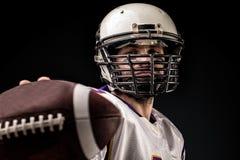 Ο φορέας αμερικανικού ποδοσφαίρου που κρατά τη σφαίρα σε δικοί του παραδίδει το μέτωπο της κάμερας Αμερικανικό ποδόσφαιρο έννοιας στοκ φωτογραφία με δικαίωμα ελεύθερης χρήσης