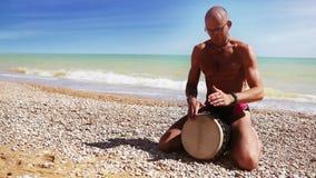 Ο φορέας τυμπάνων Djembe κτύπησε το ρυθμό στη μόνη παραλία απόθεμα βίντεο