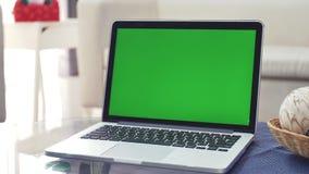 Ο φορητός προσωπικός υπολογιστής που παρουσιάζει στο πράσινο χρώμα βασική οθόνη στέκεται σε ένα γραφείο στο καθιστικό Ζουμ μέσα φιλμ μικρού μήκους