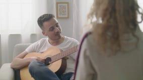 Ο φορητός πυροβολισμός του ατόμου παίζει την κιθάρα για τις φίλες του σε ένα άνετο καθιστικό απόθεμα βίντεο