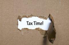 Ο φορολογικός χρόνος λέξης που εμφανίζεται πίσω από το σχισμένο έγγραφο Στοκ εικόνες με δικαίωμα ελεύθερης χρήσης