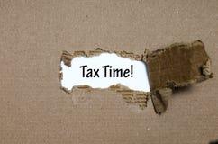 Ο φορολογικός χρόνος λέξης που εμφανίζεται πίσω από το σχισμένο έγγραφο Στοκ Φωτογραφίες