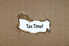 Ο φορολογικός χρόνος λέξης που εμφανίζεται πίσω από το σχισμένο έγγραφο Στοκ Εικόνες