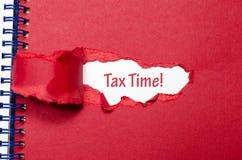 Ο φορολογικός χρόνος λέξης που εμφανίζεται πίσω από το σχισμένο έγγραφο Στοκ φωτογραφίες με δικαίωμα ελεύθερης χρήσης