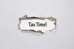Ο φορολογικός χρόνος λέξης που εμφανίζεται πίσω από το σχισμένο έγγραφο Στοκ Εικόνα