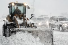 Ο φορτωτής ροδών μπροστινών μερών αφαιρεί το χιόνι από το δρόμο κατά τη διάρκεια της χειμερινής θύελλας ισχυρής χιονόπτωσης, φτωχ Στοκ φωτογραφίες με δικαίωμα ελεύθερης χρήσης