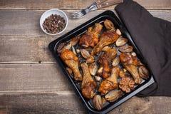 Ο φούρνος έψησε τα πόδια κοτόπουλου με τα κρεμμύδια, το σκόρδο και ένα μίγμα πιπεριών στη σκοτεινή ξύλινη κινηματογράφηση σε πρώτ Στοκ Εικόνες
