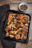 Ο φούρνος έψησε τα πόδια κοτόπουλου με τα κρεμμύδια, το σκόρδο και ένα μίγμα πιπεριών στη σκοτεινή ξύλινη κινηματογράφηση σε πρώτ Στοκ εικόνα με δικαίωμα ελεύθερης χρήσης