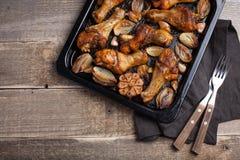 Ο φούρνος έψησε τα πόδια κοτόπουλου με τα κρεμμύδια, το σκόρδο και τα πιπέρια σε μια σκοτεινή ξύλινη κινηματογράφηση σε πρώτο πλά Στοκ Εικόνες