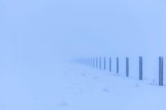 Ο φράκτης από τους συγκεκριμένους στυλοβάτες εξαφανίζεται στην ομίχλη Μυστήριο χειμερινό τοπίο Στοκ φωτογραφία με δικαίωμα ελεύθερης χρήσης