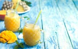 Ο φρέσκος καταφερτζής ανανά και μάγκο σε δύο γυαλιά με τα φρούτα στο α το ξύλινο αγροτικό υπόβαθρο Στοκ Εικόνα