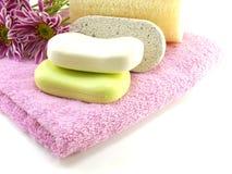 Ο φραγμός σαπουνιών και τρίβει στη ρόδινη πετσέτα λουτρών Στοκ εικόνα με δικαίωμα ελεύθερης χρήσης
