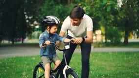 Ο φροντίζοντας πατέρας βάζει το κράνος ασφάλειας στο μικρό κεφάλι γιων του ` s διδάσκοντας έπειτα το ευτυχές αγόρι για να οδηγήσε φιλμ μικρού μήκους