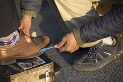 Ο φτωχός άνθρωπος γυαλίζει τα παπούτσια στοκ εικόνα