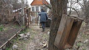 Ο φτωχός παλαιός παππούς περπατά μέσω του μπαλώματος του εδάφους στην ξεχαρβαλωμένη πύλη και το παλαιό καταρρεσμένο σπίτι απόθεμα βίντεο