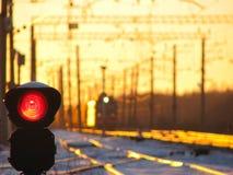 Ο φωτεινός σηματοδότης σιδηροδρόμων παρουσιάζει μπλε σήμα στο σιδηρόδρομο και το σιδηρόδρομο με το φορτηγό τρένο ως υπόβαθρο Στοκ Εικόνα
