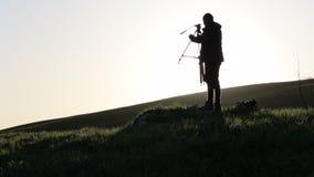 Ο φωτογράφος ανοίγει το μηχανισμό και τα σύνολα τρίποδων - επάνω κάμερα στην κορυφή του πράσινου λόφου απόθεμα βίντεο