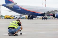 Ο φωτογράφος κάνει τη φωτογραφία του airbus A330 των αερογραμμών Αεροφλότ στο αεροδρόμιο Αεροπλάνο που επισημαίνει, χόμπι, αεροπο στοκ φωτογραφία