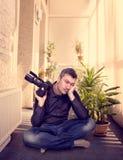 Ο φωτογράφος με τη συνεδρίαση καμερών σε μια γιόγκα θέτει Στοκ Εικόνες