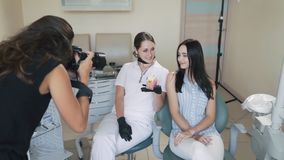 Ο φωτογράφος παίρνει τις εικόνες του οδοντιάτρου και του ασθενή στην οδοντική κλινική, σε αργή κίνηση απόθεμα βίντεο