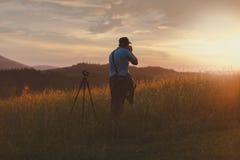 Ο φωτογράφος πυροβολεί το τοπίο στο ηλιοβασίλεμα Στοκ Φωτογραφίες