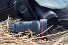 Ο φωτογραφικός φακός βρίσκεται σε μια θυμωνιά χόρτου, έννοια επαρχίας protographer στοκ εικόνες