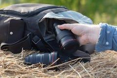 Ο φωτογραφικός φακός βρίσκεται σε μια θυμωνιά χόρτου, έννοια επαρχίας protographer στοκ φωτογραφίες με δικαίωμα ελεύθερης χρήσης