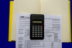 Ο φόρος διαμορφώνει 1040, υπολογιστής, σημειωματάριο σε ένα μπλε υπόβαθρο στοκ φωτογραφία με δικαίωμα ελεύθερης χρήσης