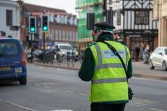 Ο φύλακας κυκλοφορίας περπατά κάτω από μια πολυάσχολη κεντρική οδό στο UK στοκ φωτογραφία με δικαίωμα ελεύθερης χρήσης
