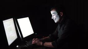 Ο χάκερ στη μάσκα χαράσσει το πρόγραμμα ο ψηφιακός εκβιασμός παίρνει την πρόσβαση σε άλλες πληροφορίες ανθρώπων ` s Υπολογιστής απόθεμα βίντεο