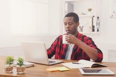 Ο χαλαρωμένος μαύρος επιχειρηματίας στο περιστασιακό γραφείο, εργασία με το lap-top, πίνει τον καφέ Στοκ εικόνες με δικαίωμα ελεύθερης χρήσης
