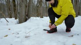 Ο χαμηλός πυροβολισμός του γενειοφόρου δένοντας παπουτσιού αθλητών δένει jogging στο χειμερινό δάσος απόθεμα βίντεο