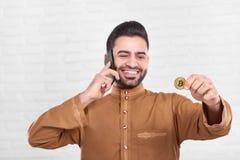 Ο χαμογελώντας αραβικός επιχειρηματίας κρατά το χρυσό bitcoin Στοκ Εικόνα