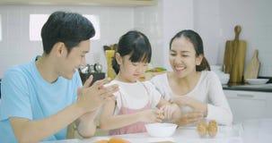 Ο χαμογελώντας ασιατικοί πατέρας, η μητέρα και η κόρη απολαμβάνουν ένα υγιές γεύμα στην κουζίνα από κοινού απόθεμα βίντεο
