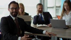 Ο χαμογελώντας γενειοφόρος επιχειρηματίας στο μαύρο κοστούμι κάθεται από το γραφείο Οι συνάδελφοι στο υπόβαθρο απόθεμα βίντεο
