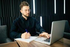 Ο χαμογελώντας επιχειρηματίας με το φορητό προσωπικό υπολογιστή και γράφει την ειδοποίηση στα έγγραφα στο γραφείο Στοκ φωτογραφία με δικαίωμα ελεύθερης χρήσης