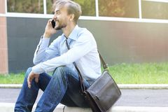 Ο χαμογελώντας επιχειρηματίας στα περιστασιακά ενδύματα με τη συνοπτική τσάντα δέρματος κάθεται στοκ εικόνες